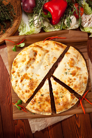 Pizza Calzone with Chicken and Vegetables on Parchment photo