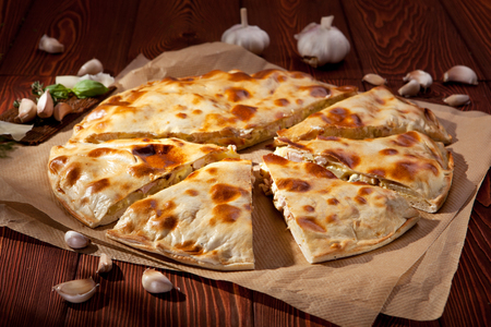 Pizza Calzone with Chicken and Cheese on Parchment photo