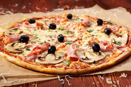Pizza with Mozzarella, Bacon, Mushrooms and Olives photo