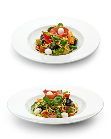 pasta isolated: Spaghetti with Vegetables, Ham, Black Olives, Rucola and Pesto Sauce Stock Photo