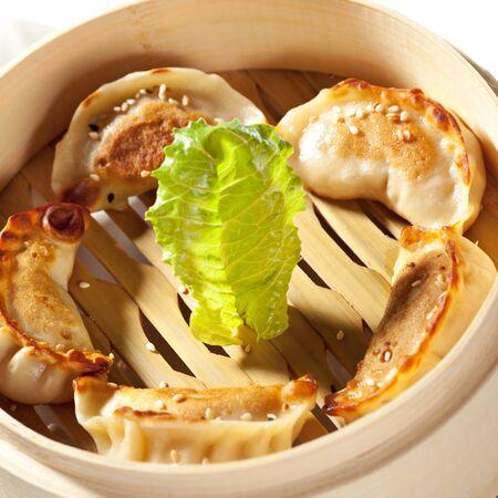 gyoza: Seafood Fried Dumpling - Gyoza  Garnished with Sauce, Tomato and Parsley