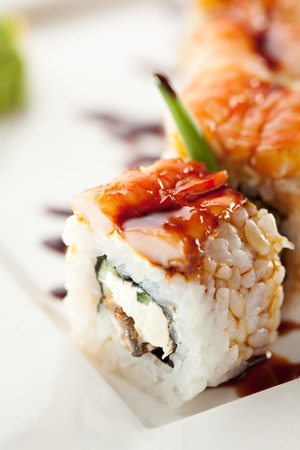 grig: Japanese Cuisine - Sushi Roll with Cucumber, Cream Cheese and Smoked Eel inside  Topped with Shrimp  Garnished with Unagi Sauce Stock Photo