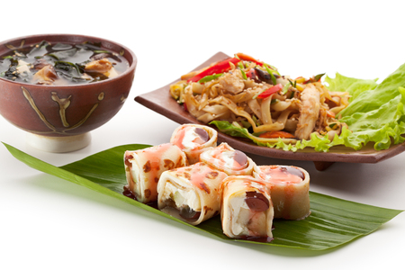 Japanese Meal - Noodles with Chicken, Dessert Fruit Maki Sushi and Miso Soup photo