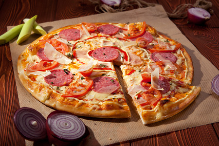 Pizza with Ham, Salami, Tomatoes and Mozzarella Cheese