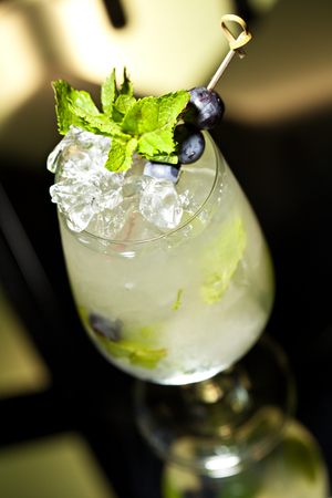 green glass bottle: Cocktail with Vodka and White Wine, Grapes, Various Syrup and Lime Juice