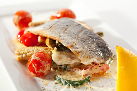 Fillet of Seabass with Tomato and Mussels Sauce. Garnished with Vegetables photo