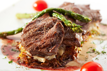 Grilled Beef with Potato and Mushrooms. Garnished with Cherry Tomatoes and Asparagus photo
