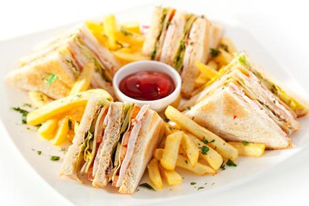 Club Sandwich met kaas, ingemaakte Cucmber, tomaat en gerookt vlees. Gegarneerd met Frieten
