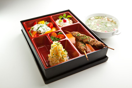 bento box: Japanese Meal in a Box - Salad, Skewered Meat and Mashed Potato and Dessert Stock Photo