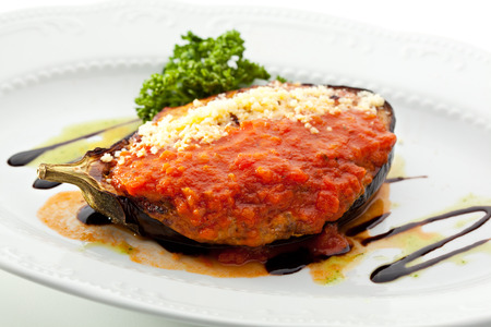 Stuffed Eggplant with Spicy Sauce. Garnished with Fresh Parsley photo