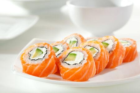maki: Philadelphia Maki Sushi made of Cream Cheese and Avocado inside. Salmon outside