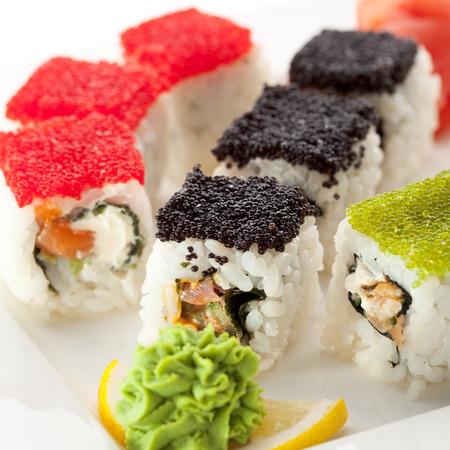 Maki Sushi with Fresh Salmon, Eel and Tuna inside. Topped with Tobiko photo