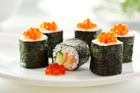 cuisines: Sake Maki Sushi - Roll with Fresh Salmon and Cucumber inside. Topped with Salmon Caviar Stock Photo