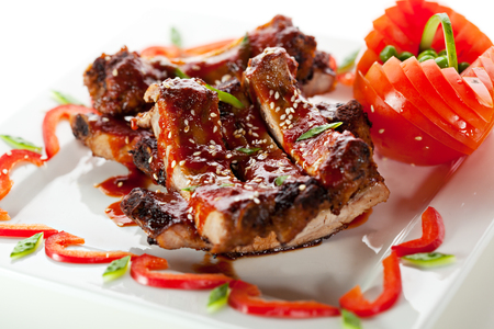 bbq ribs: Hot Meat Dishes - BBQ Ribs with Tomatoes and Spicy Sauce Stock Photo