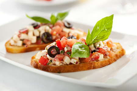 basil: Italian Appetizer Bruschetta with Tomatoes, Cheese and Basil Stock Photo