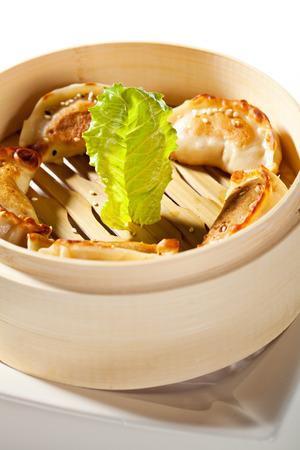 gyoza: Seafood Fried Dumpling - Gyoza. Garnished with Sauce, Tomato and Parsley Stock Photo