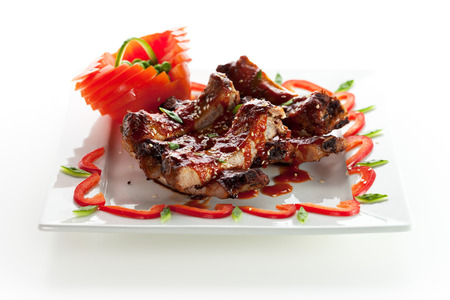 Hot Meat Dishes - BBQ Ribs with Tomatoes and Spicy Sauce Archivio Fotografico