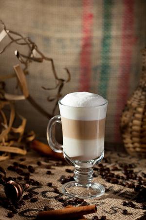 latte macchiato: Latte Macchiato with Coffee Beans and Cinnamon Stock Photo
