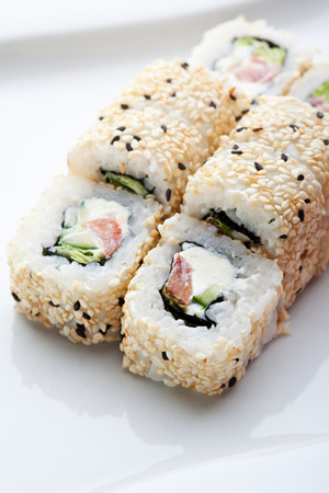 ouside: Maki Sushi - Roll made of Smoked Salmon, Cream Cheese, Cucumber and Spring Onion inside. Sesame ouside