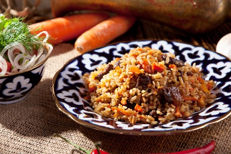 meat dish: Pilaf - Rice with Meat and Vegetables. Garnished with Onions and Tomatoes Salad