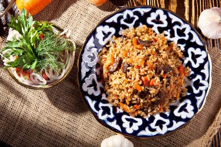 onion: Pilaf - Arroz con carne y verduras. Adornado con las cebollas y los tomates de ensalada