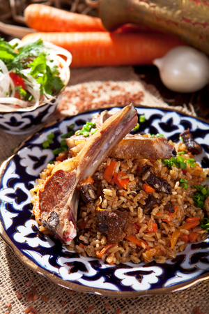 lamb: Pilaf - Rice with Lamb Chops and Vegetables. Garnished with Onions and Tomatoes Salad