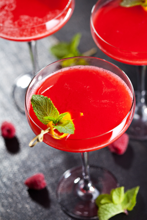 citron: Red Alcoholic Cocktail with Raspberry Gin. Garnished with Fresh Mint Leaves and Lemon Citron Stock Photo