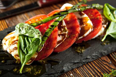 Ensalada Caprese - ensalada con tomates, queso mozzarella, albahaca, espárragos y balsámico. Aderezo de ensalada con salsa de pesto Foto de archivo - 52009036