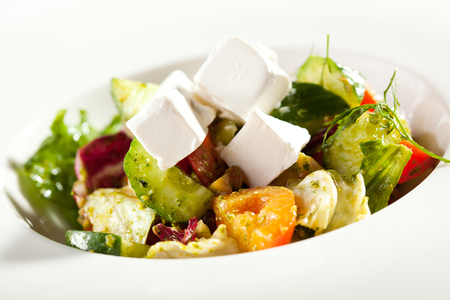 feta cheese: Greek Salad - Feta Cheese, Tomatoes, Salad Leaves,  Olive and Vegetables Stock Photo