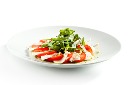 isolated white background: Caprese Salad - Salad with Tomatoes, Mozzarella Cheese and Rocket Salad. Salad Dressing with Pesto Sauce and Pine Nuts