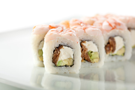 topped: Japanese Cuisine - Sushi Roll with Avocado, Cream Cheese and Smoked Eel inside. Topped with Shrimp Stock Photo