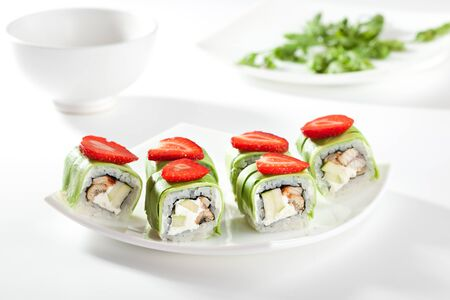 sushi: Maki Sushi - Roll made of Cream Cheese, Apple and Eel inside. Avocado outside. Topped with Strawberries