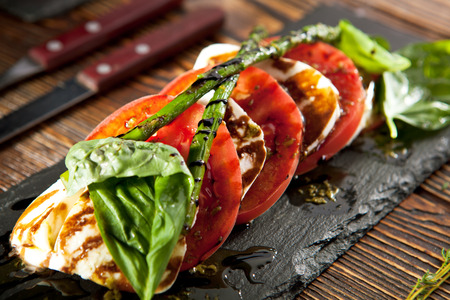 knife tomato: Caprese Salad - Salad with Tomatoes, Mozzarella Cheese, Basil, Asparagus and Balsamic. Salad Dressing with Pesto Sauce