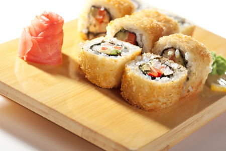 fried: Tempura Maki Sushi - Deep Fried Roll made of Crab Meat, Paprika and Lettuce inside. Served on Wooden Plate
