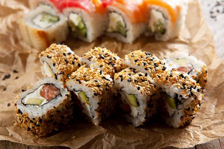 sushi: Maki Sushi - Roll with Smoked Salmon, Cream Cheese and Avocado inside. Sesame outside Stock Photo