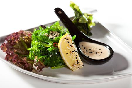 ajonjoli: Cocina japonesa - ensalada de algas Chuka con salsa de nueces. Servido con limón y sésamo Foto de archivo