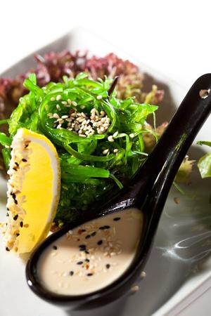 japanese cuisine: Japanese Cuisine - Chuka Seaweed Salad with Nuts Sauce. Served with Lemon and Sesame Stock Photo