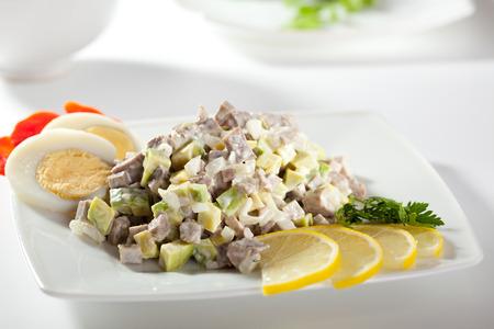 russian salad: Olivier ensalada rusa vestida con rodaja de limón y huevo Foto de archivo
