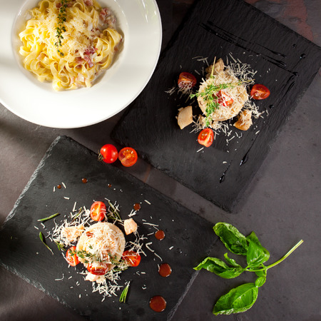 main course: Italian Main Course. Pasta and Risotto on Black Slate Background Stock Photo