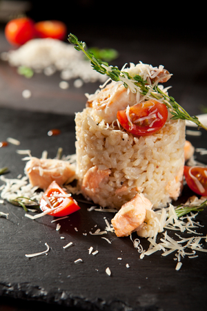 black dish: Gourmet Seafood Risotto with Parmesan and Cherry Tomato