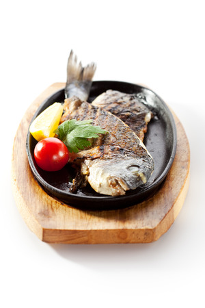 gilt head: Pan-Fried Gilt Head Bream with Lemon Slice and Tomato Stock Photo