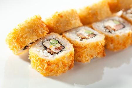 eating food: Tempura Maki Sushi - Deep Fried Roll made of Fresh Raw Salmon, Avocado and Cream Cheese inside
