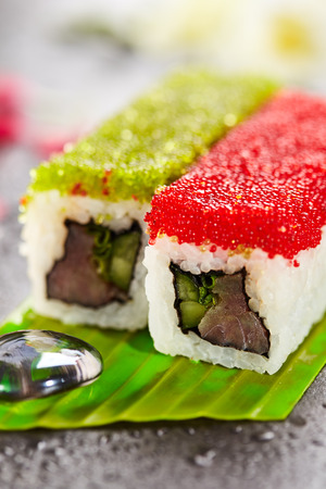 fish type: Tobiko Spicy Maki Sushi - Hot Roll Topped with various type of Tobiko (flying fish roe). Tuna, Cucumber and Green Lettuce inside. Served on Banana Leaf with Flowers