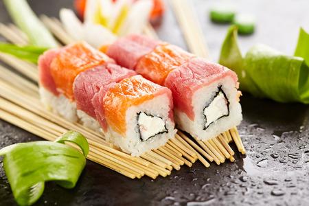 adentro y afuera: Salmon and Tuna Maki Sushi - Roll made of Cream Cheese and Shrimp (ebi) inside. Fresh Salmon and Tuna outside Foto de archivo