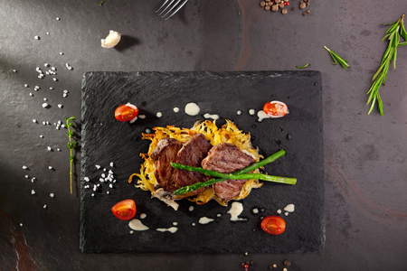 Grilled Beef Steak with Potato and Mushrooms. Garnished with Cherry Tomatoes and Asparagus