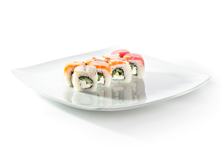 Rainbow Maki Sushi - Roll with Cucumber and Cream Cheese inside. Tuna, Salmon and Eel outside Stock Photo