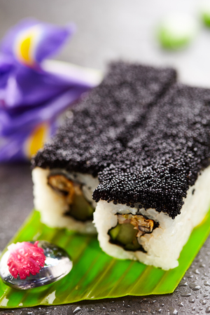 roe: Maki Sushi with Prawn, Cucumber and Fried Seafood inside. Topped with Black Tobiko (flying fish roe). Served on Banana Leaf with Flowers