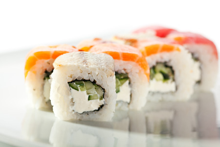 rainbow fish: Rainbow Maki Sushi - Roll with Cucumber and Cream Cheese inside. Tuna, Salmon and Eel outside Stock Photo