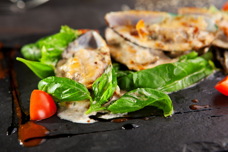 Baked Mussels with Spicy Sauce. Garnished with Cherry Tomato and Salad Leaves