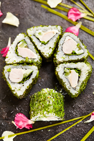 asian natural: Green Maki Sushi - Roll made of Chicken, Cream Cheese, Lettuce and Cucumber inside. Dill outside. Asian Food and natural Flower Concept